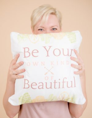 Blond model holding pillow just below her eyes